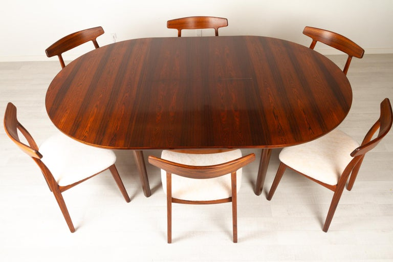 This dining room set consists of the following table and six chairs:  Vintage Danish round extendable rosewood dining table, 1960s Danish modern round rosewood dining table with hidden double butterfly leaves. Extremely expressive and beautiful