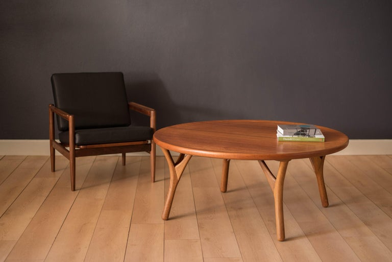 Mid-Century Modern coffee table in teak made in Denmark, circa 1950s. This statement piece has a unique sculpted raised edge and contrasting solid oak tripod legs.    Offered by Mid Century Maddist