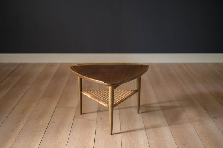 Mid Century triangular occasional table or guitar pick side table designed by Poul Jensen imported by Selig, Denmark. This piece features a unique walnut raised edge top and lower tier magazine shelf made of woven cane.    Offered by Mid Century