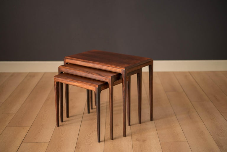 Mid-Century Modern nesting tables by Johannes Andersen for CFC Silkeborg made in Denmark. This versatile set features Brazilian rosewood with contoured edges and tapered legs.  Largest end table: 23.75