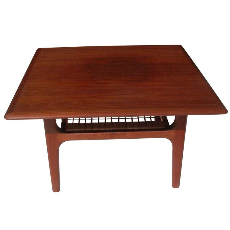 Vintage Danish side table by Trioh. 2-tier teak table featuring a cane shelf.