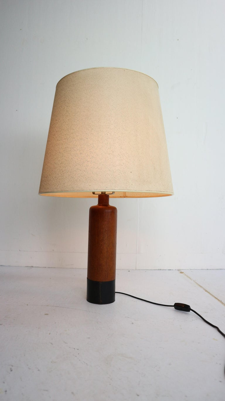 Cylindrical table lamp by ESA, Denmark, circa 1960. Solid teak feed complemented by a black-leather wrapped base.  Two lamp sockets and the original vintage shade.