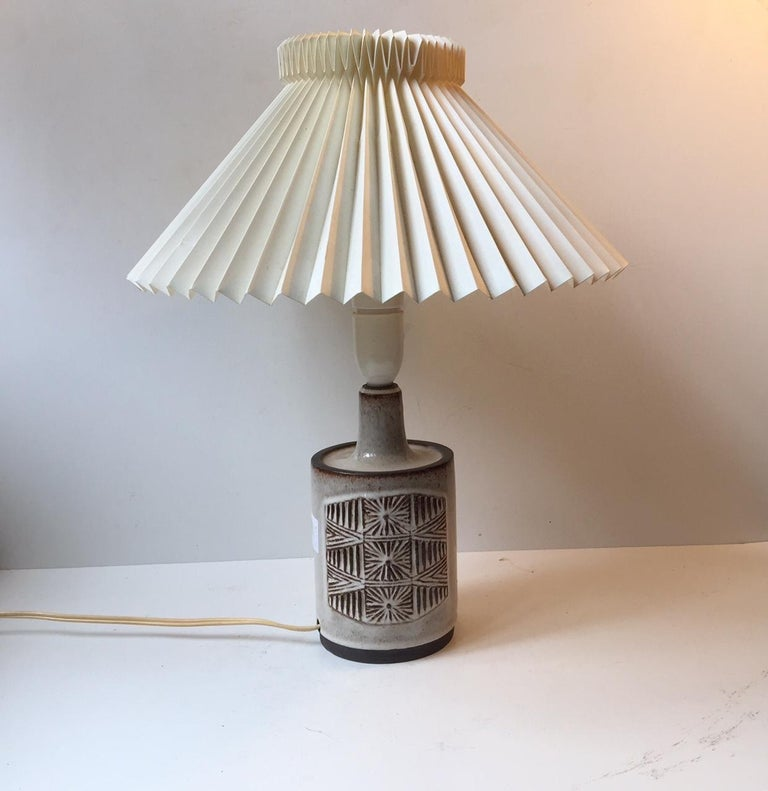 Vintage Danish Stogo stoneware table lamp with sunburst center motif. It was designed by ceramist H. Gottschalk-Olsen in the 1970s and manufactured at Stogo Studio. Stamped with both maker marks and designer initials to the base. The table lamp is