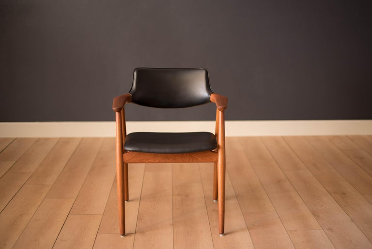 Mid-Century Modern armchair designed by Svend Åge Eriksen for Glostrup Møbelfabrik model GM 11. Features sculpted teak arms cushioned with a black vinyl backrest and seat. Perfect to use in the office or as a captain dining chair.