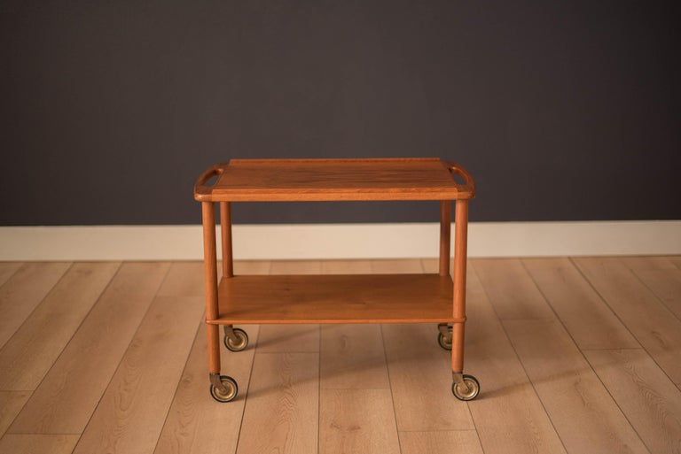 Mid-Century Modern teak serving tea trolley or bar cart made by Bowa, Denmark, circa 1960s. This piece features two sculpted handles on each side and easy to roll original casters. Equipped with a lower tier shelf for extra display storage.