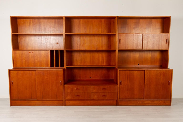Vintage Danish teak bookcase by Clausen & Søn Silkeborg, 1960s Large modular bookcase in three sections, each with top and bottom module. Iconic bow tie style pulls on drawers and sliding doors. Contains two large cabinets with sliding doors,