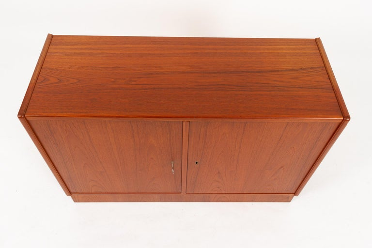 Vintage Danish Teak Cabinet 1960s. Midcentury modern teak sideboard with two doors and two compartments. Each compartment is divided by one shelf. Shelves are adjustable by hand. Each door has a lock, and one key is included, fits both locks.
