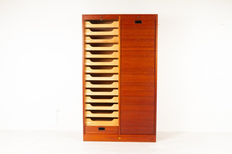 Vintage Danish teak cabinet with tambour doors, 1960s Danish modern large double filing cabinet with vertical sliding tambour front in teak made by Bjerringbro Savværk in Denmark. Two separate compartments, one with 14 drawers and one with three