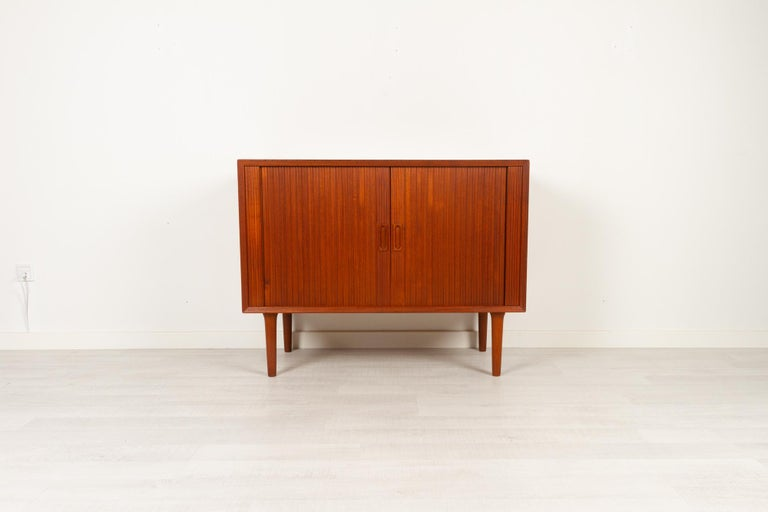 Vintage Danish teak cabinet with Tambour doors by Lyby Møbler, Denmark 1960s Elegant and stylish Danish Mid-Century Modern cabinet with beautifully crafted tambour doors. Frame with bevelled edges and grips in solid teak. Round tapered legs with