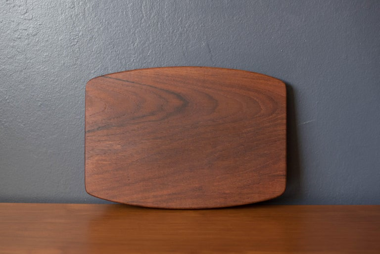 Mid-Century Modern serving tray platter manufactured by Wiggers, Denmark. Unlike most Danish trays, this was constructed of one solid piece of teak with clever cutout handles underneath. Perfect to display for your home decor collection or as a