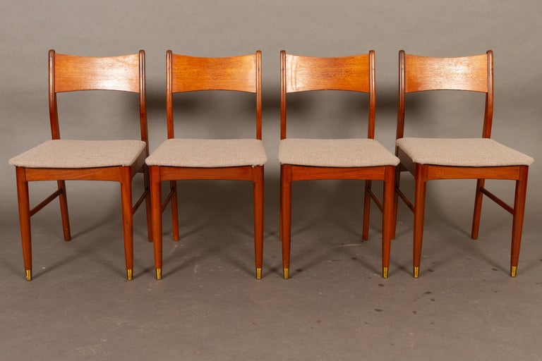 Vintage Danish teak dining chairs 1950s set of 4 Set of four elegant Danish Mid-Century Modern dining chair with solid teak frame and backrests in teak veneer. Legs are rounded and front legs have round brass shoes. Seats are upholstered with grey