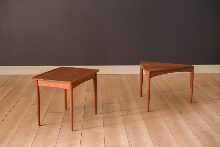 Mid-century modern teak side table manufactured by Mobelintarsia, Denmark, circa 1960s. Features a sculpted raised lip with a contrasting edge band well-fitted by finger joinery. Finished with classic dowel legs and a supporting apron.    Offered by