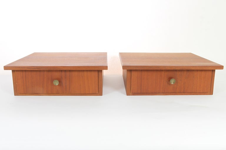 Vintage Danish teak hanging shelves with drawer, 1960s, set of 2. Matching pair of midcentury pair of shelves in teak veneer. Drawer with brass pulls. Ideal for bedside tables, night stands, shelves or in a small hallway. Good vintage condition.