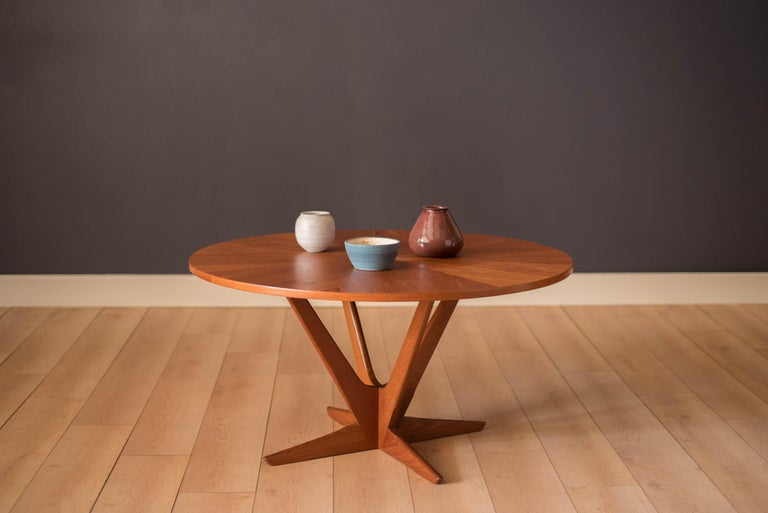 Mid-Century Modern round coffee or occasional table by Soren Georg Jensen for Kubus. The top features a stunning radial teak veneer pattern supported by a unique sculptural atomic base. Perfect to use as center table or an entryway foyer piece.
