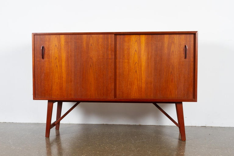 Vintage Danish teak sideboard, 1960s Small and elegant Mid-Century Modern lowboard with double sliding doors and shelves. Very nice warm and golden veneer color. Sculpted grips in solid teak. Slightly slanted legs. Frame and legs in solid teak. A