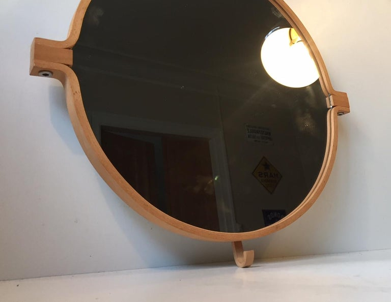 A bend wood wall mirror in beech. Designed and manufactured by Indan in Denmark during the 1980s. This is design number: 009 and it features a practical built in hook to the bottom.