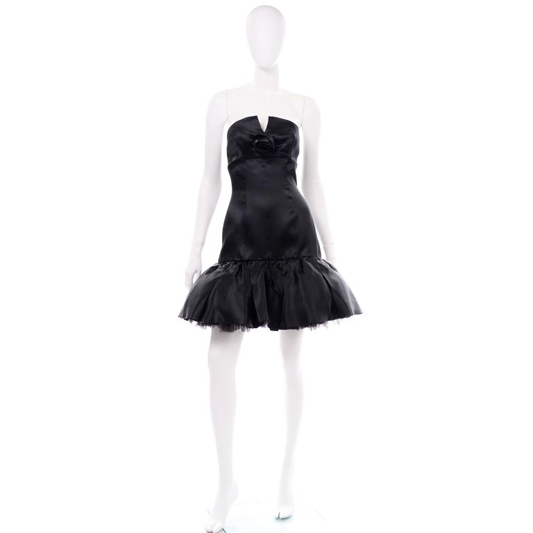 This beautiful soft black silk satin vintage David Fielden dress has a tulle petticoat for fullness and a round strapless with a small v-cut down the center. There is an empire waistline and a center focus is the satin silk rose. There is metal