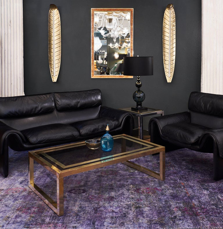 Superb Swiss made Vintage black leather sofa by iconic Swiss de Sede. The design of the seat, back, and arm cushions create a subtle touch of detail, while the overall clean curvilinear design and openness under the seat finalize the modern and