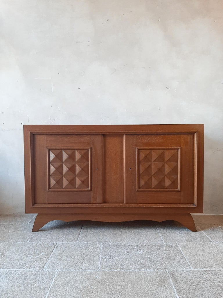 Vintage design sideboard by Charles Dudouyt in oak with a French polish finish, 1940s-1950s. This beautiful cabinet in Brutalist style has 2 doors and shows a large storage space with shelves on the inside. The compartment on the right has a
