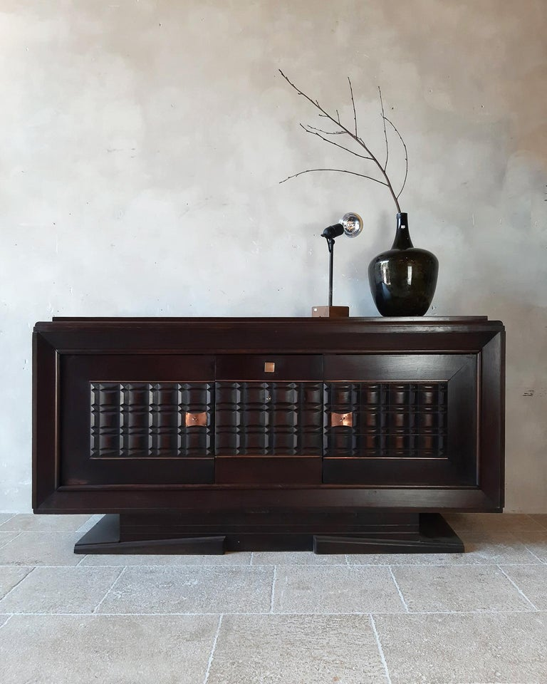 Vintage design sideboard by Charles Dudouyt in dark oak, 1940s-50s. The doors of this beautiful credenza are cut out in graphic and geometric shapes. With copper-coloured details.  Dimensions: H 100 x W 200 x D 54 cm.