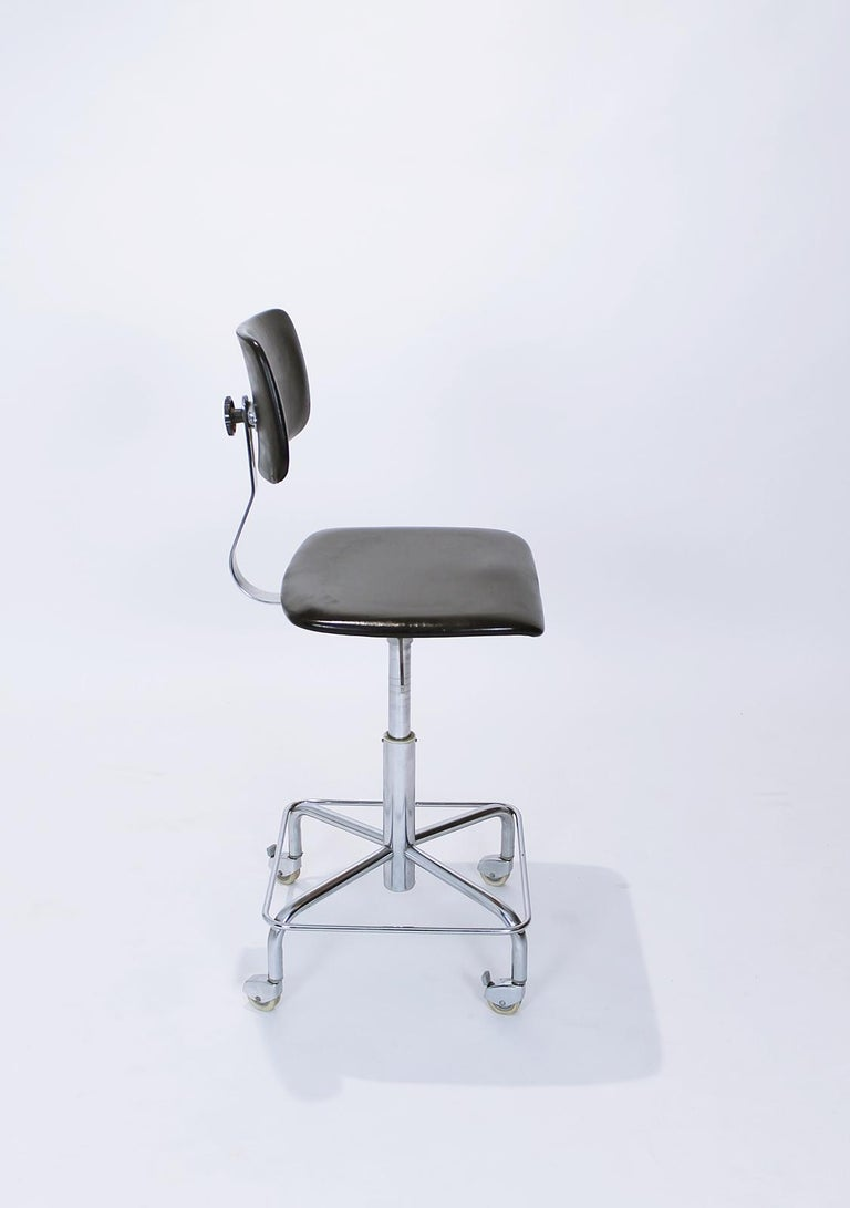 Vintage mid century rolling desk swivel chair by Bremshey, Germany. This chair has a chromed steel frame, the back and seat are black vinyl. The chair is height adjustable with gas spring. The chromed metal frame has four wheels with Haco parking