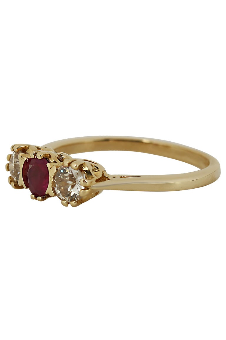 A tailored three stone ring featuring a center ruby weighing approximately 0.35 carat illuminated by two European cut diamonds weighing approximately 0.40 carat total mounted in 14 karat yellow gold. Current size 6.75.