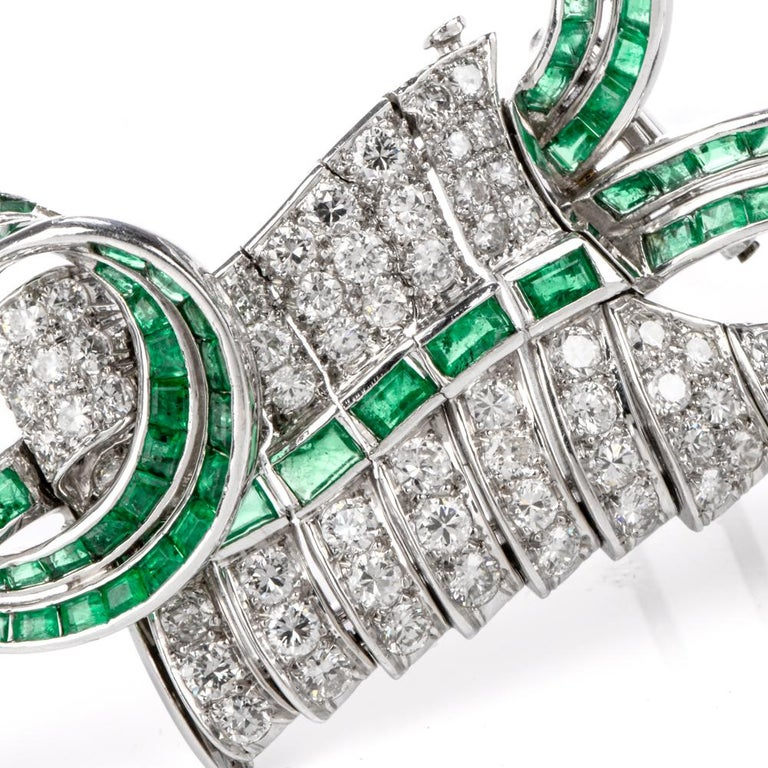 "This artistic vintage diamond and emerald brooch is crafted in solid platinum, weighing 35.4 grams and measuring 2.75"" long x 51mm wide. Pave-set with 75 round-cut diamonds, collectively weighing approximately 5.10 carats, graded G-H  color and"