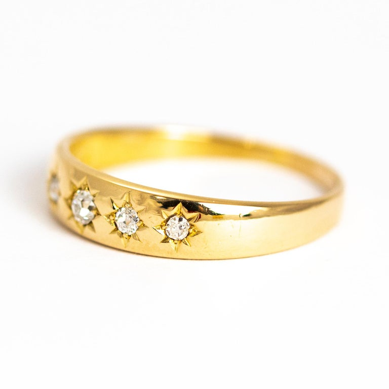 This delicate 18ct gold band hold five bright shimmering diamonds all beautifully sat in star settings. Simple and stunning. Made in Birmingham, England.  Ring Size: Q or 8 Band Width: 4.5mm