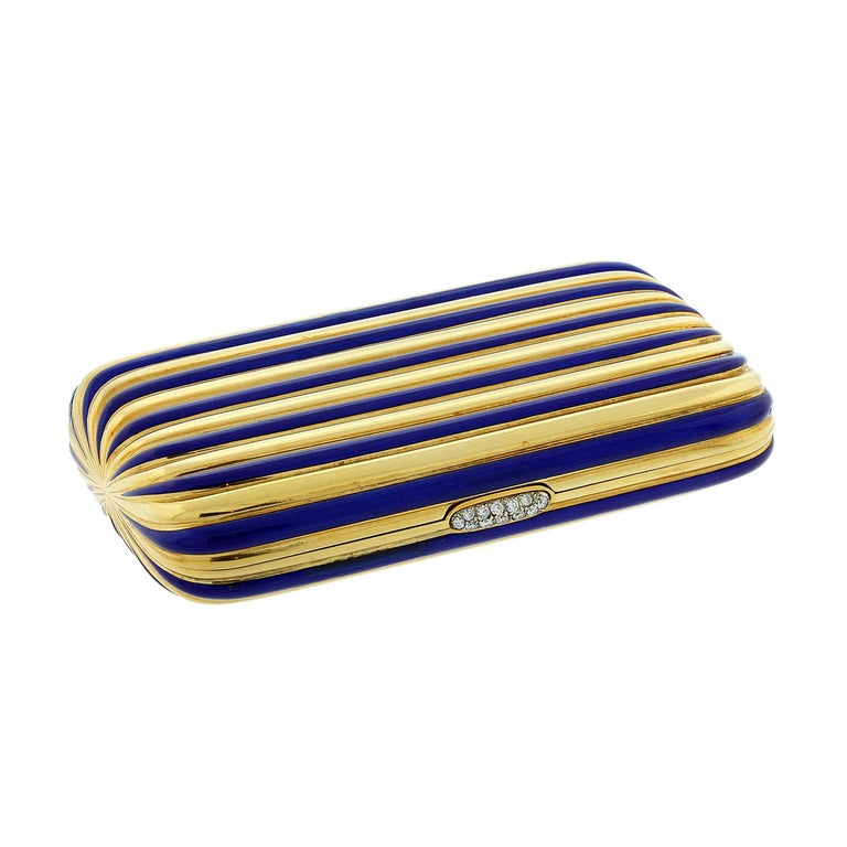 This exceptional compact features a striped design in 18K yellow gold and vibrant blue enamel. The case opens with a press on the diamond clasp.  Inside features a clean yellow gold striped design.  As a multi-use case it can be used to hold cards,