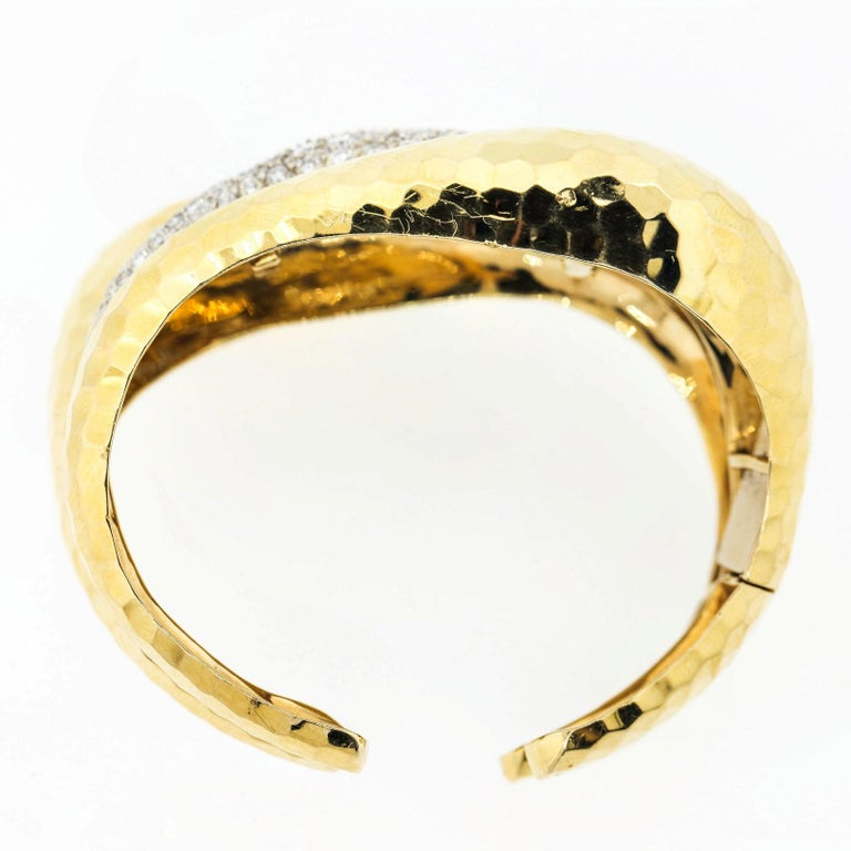 Impressive 1970s 14KT yellow and white gold hand hammered cuff.  The bracelet is created as a triple row of flowing swirls, accented in the middle with 5.75 carats of pave set Round Brilliant Cut Diamonds; all of H/I color - SI clarity.   One end