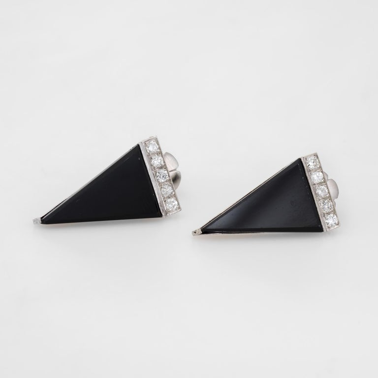Striking pair of vintage triangle earrings, crafted in 900 platinum.   Onyx is triangular cut and measures 19mm x 11mm, accented with a row of round brilliant cut diamonds. The 10 diamonds are estimated at 0.04 carats each, totaling an estimated