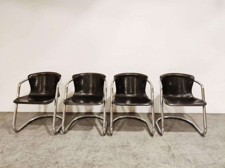 Set of 4 saddle leeather dining chairs designed by Willy Rizzo for Cidue..  The chairs have a beautifully shaped chrome frame and come with the original black leather seats.  Good condition.  This is a rare model.  The chairs still look up