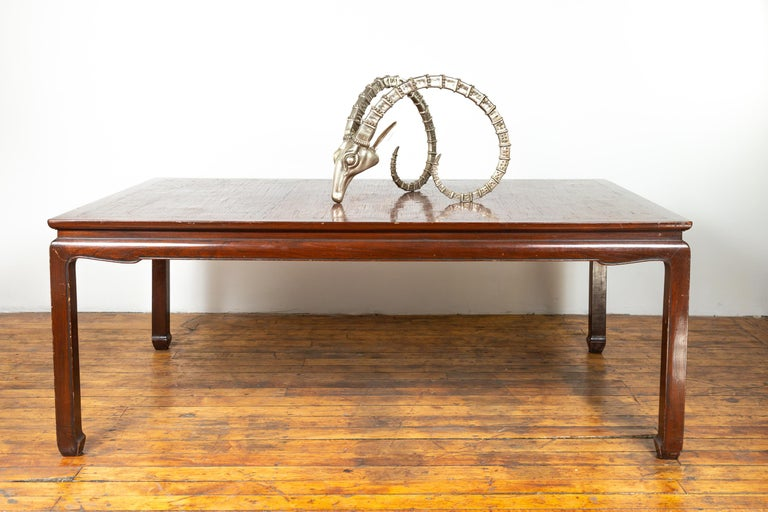 A vintage Thai dining table from the mid-20th century, with open mat top inlay and horsehoof legs. Born in Thailand during the mid-century period, this elegant dining table features a rectangular open mat inlaid waisted top sitting above an arched