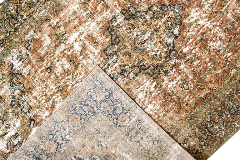 A mid-20th century vintage distressed Persian area rug with a brick-red field and medallion design. This hand knotted wool rug measures 9'6