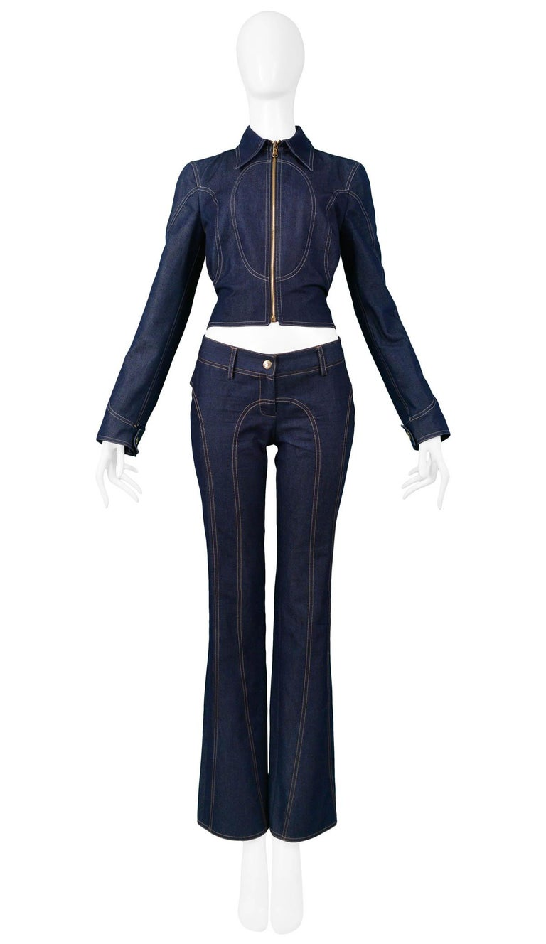 Vintage Dolce & Gabbana blue denim western-style zip-up jacket and flared pant ensemble. Jacket and pants feature circular contrast top-stitching detail throughout and gold logo buckle at back. Collection 2001.  Excellent Vintage