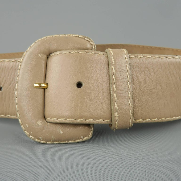 Vintage DONNA KARAN waist belt comes in light taupe gray leather with contrast stitching and a covered buckle. Wear throughout. As-is. Made in Italy.   Fair Pre-Owned Condition. Marked: Medium   Length: 38 in. Width: 2 in. Fits: 27-32 in.