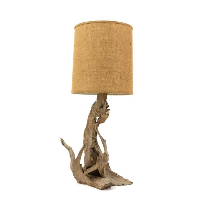 Vintage driftwood table lamp with original period burlap drum shade. USA, circa 1960.  Dimensions: 17 inches W × 9 inches D × 39.5 inches H.