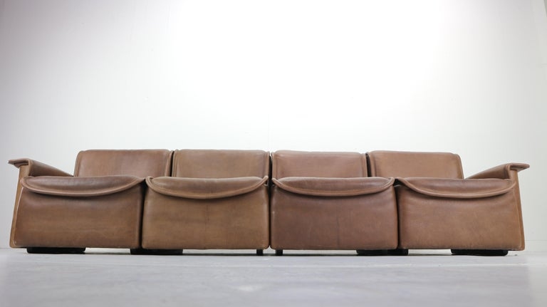 Rare four-seat sofa model DS-12 designed by design team at De Sede. Produced by De Sede in Switzerland in 1970s. The sofa seating is made of thick brown leather and consists of four easily movable peaces. Scandinavian Modern design.