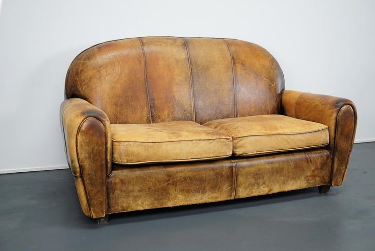This cognac sheeps leather sofa was designed and handmade in the Netherlands. It retained a rich patina and is very comfortable. It remains in a good vintage condition.