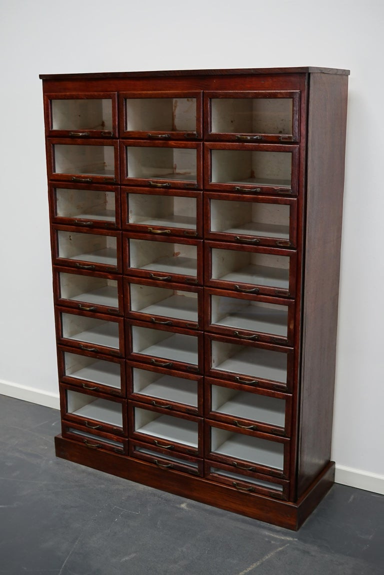 This haberdashery cabinet was produced during the 1930s in the Netherlands. This piece features 27 paper covered drawers in mahogany stained oak with glass fronts, brass handles and name card holders. It was originally used in a shop for sewing