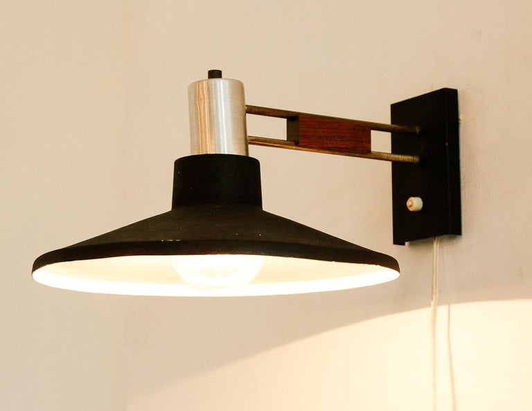 Vintage wall sconce from Holland, 1960s. Black textured dish-shaped shade, silver hardware and teak detail.