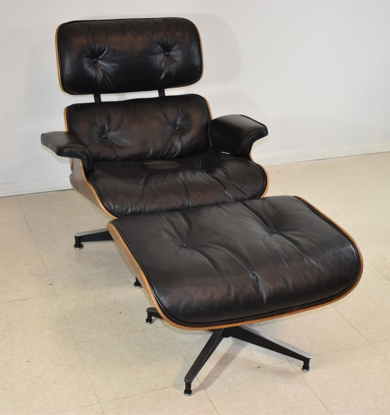 Vintage Eames black leather and rosewood chair and ottoman. Original finish. One button is loose.
