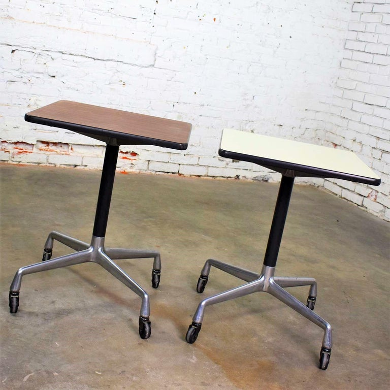 Two handsome square rolling side tables designed by Charles and Ray Eames for Herman Miller. Both with universal bases. One has a white laminate top and one has a faux wood grain laminate top. Each is in wonderful vintage condition with the normal