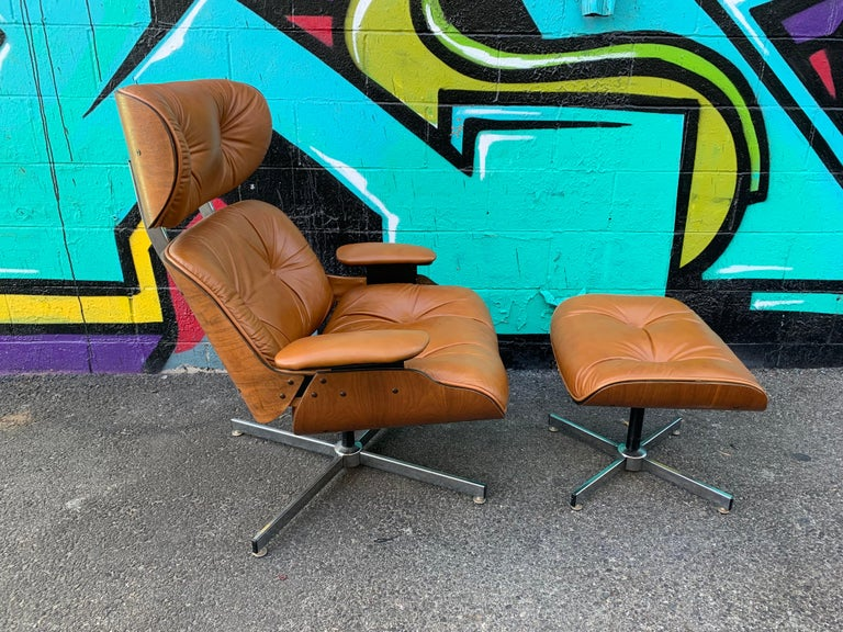 A vintage Eames style lounge chair and ottoman by Plycraft features the original leather the seat shows. Minor scuff marks (shown in photo) walnut veneer in great condition, circa 1960s.