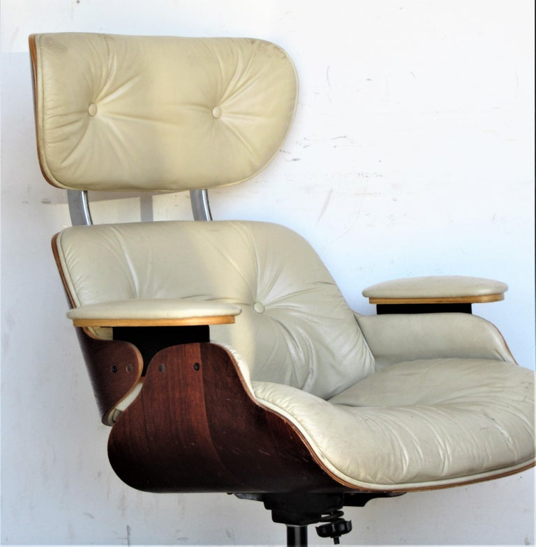 Eames style bent stacked laminated plywood swivel tilting walnut lounge chair and ottoman - good original vintage condition, circa 1960 - 1970. We are pretty sure the chair is by Plycraft, We are not sure about the manufacturer of the ottoman, it is