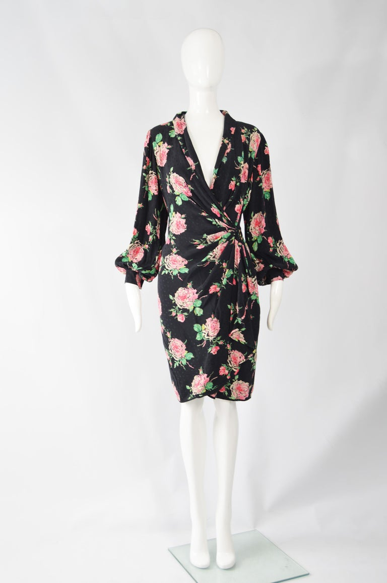 An incredibly feminine and elegant vintage dress from the 1980's by master of draping and print, Emanuel Ungaro. Made in Italy, this luxurious dress is in a light and airy black silk with a bold but current rose print and a subtle polka dot satin