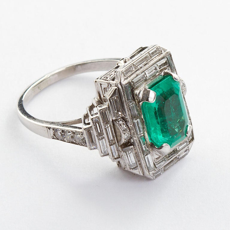 An Art Deco inspired platinum vintage ring set with an approx. 4.00 carat octagon emerald and set with surrounding baguette cut diamonds. Ring size 7 (can be resized down to 4).  No. TMWJ-8318