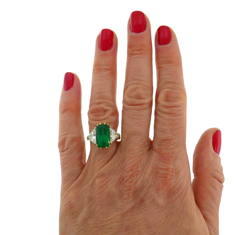 Classy and timeless three-stone ring. The ring features a beautiful color cushion cut natural emerald flanked with two trillion cut diamonds. The emerald measures 13.57 x 8.02 x 6.32 mm and comes with a Guild Laboratories Gemstone Identification