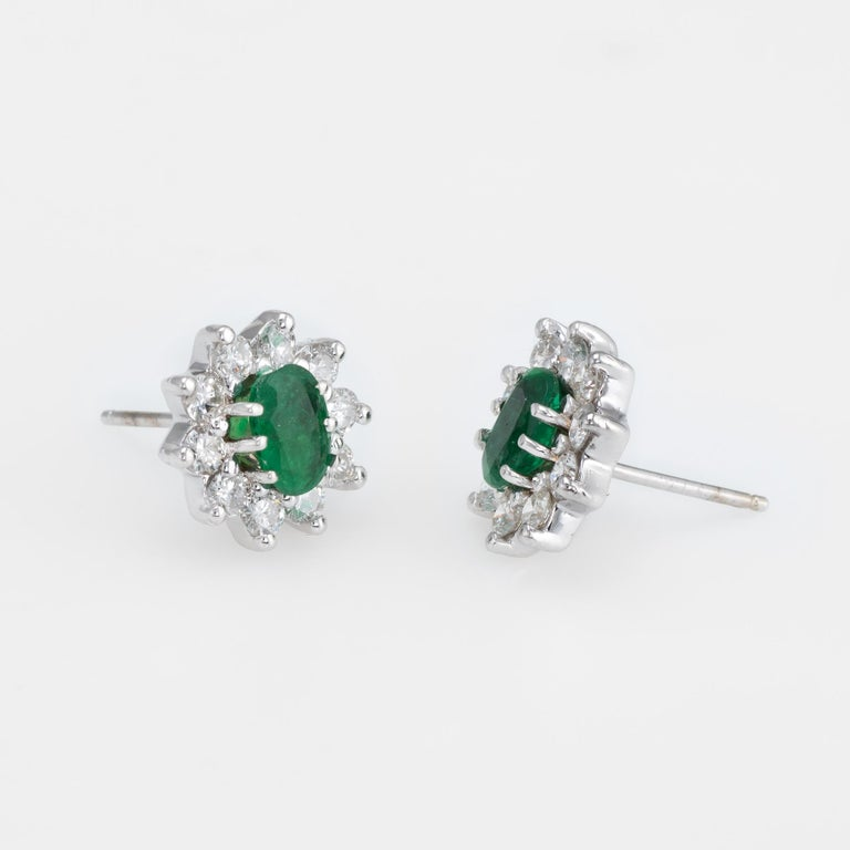 Elegant pair of estate emerald & diamond oval stud earrings, crafted in 14k white gold.   Oval faceted emeralds measure 6mm x 5mm (estimated at 0.50 carats each - 1 carat total estimated weight). The 20 round brilliant cut diamonds (10 per earring)