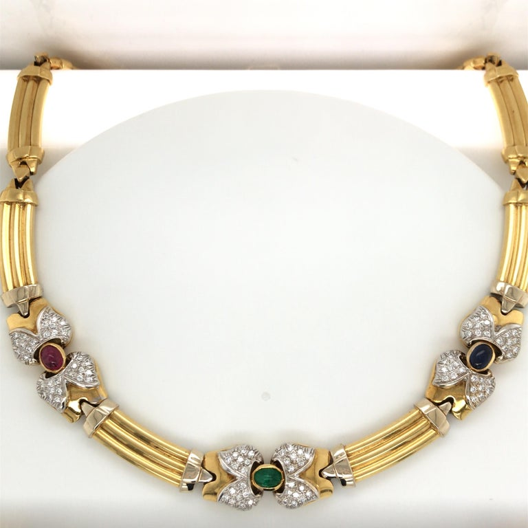 Vintage 18K Yellow gold necklace featuring three ovals of an Emerald, Sapphire and Ruby flanked with round brilliants in a bow motif.